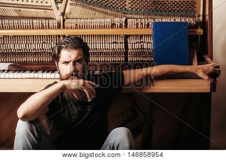 Bearded Man With Glass Near Wood Piano