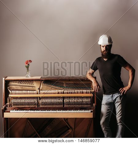 Bearded Man In Helmet Near Wood Piano