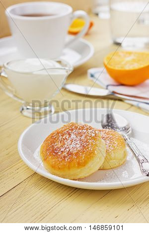 Fritters of cottage cheese with sour cream on a wooden background.