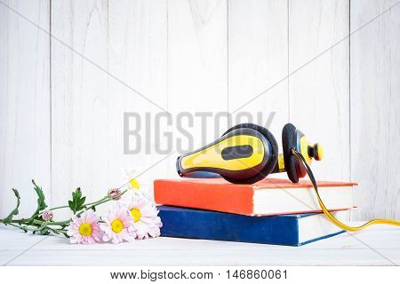 Headphones on books with Flowers on white wood background