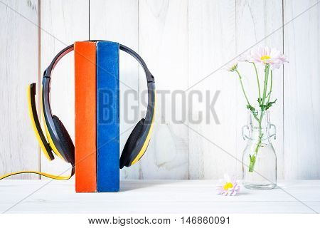 Headphones on book with Flowers on white wood