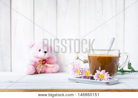 Coffee cup and a mobile phone with flowers on the white wooden table.