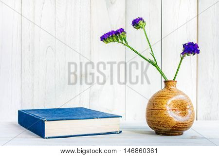 books or journal with flowers arranged on a neutral white painted desk.