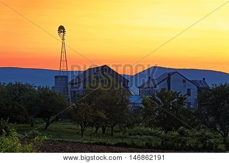 A beautiful sunrise on a rustic Amish farmstead with a windmill in Pennsylvania, USA.