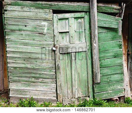 Photography of a old wooden barn green door