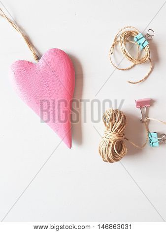 pink wooden heart with rope and clips on a white background