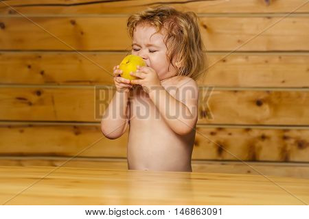 Cute Small Boy Child Eating Yellow Apple
