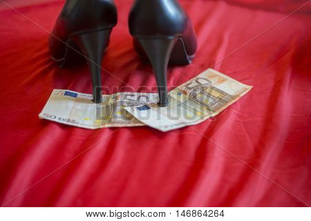 Heels Of Black Shoes On 50 Euro Banknot On Red Bed