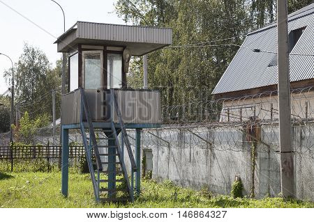 Watch tower and white wall with metal barbed fence in abandoned prison