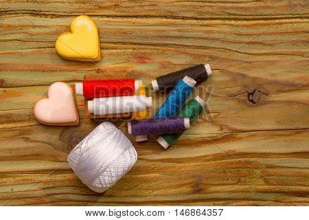 Many bobbins of bright colorful cotton threads for sewing homemade cookies in heart shape and hank of yarn on wooden background