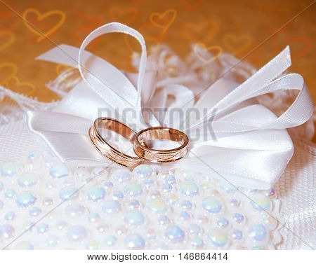 Gold wedding rings on the pincushion. Background with hearts