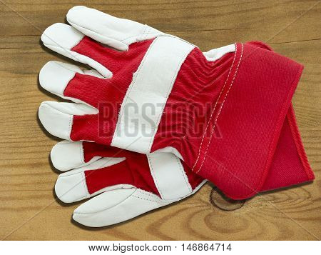 Two new red and white working gloves on wooden board
