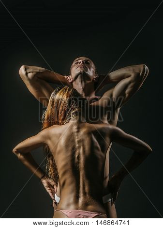 young sexy couple of pretty slim sporty woman with long hair and handsome muscular man with fit body and bare chest with torso in panties on studio background