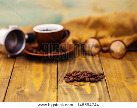 brown roasted or fried coffee beans in heap on wooden table near cup pot and glasses with no people on wood background