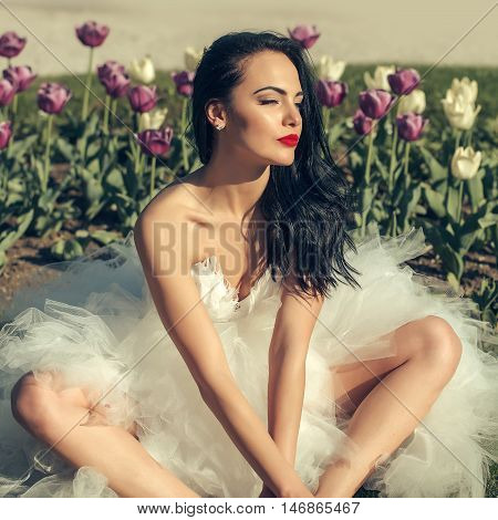 Beautiful bride brunette woman with long hair in fashion white wedding dress sits in flowerbed on sunny summer day