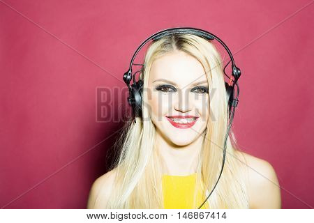 young woman or girl dj with blonde hair and red lips on pretty smiling sexy face in yellow shirt with musical stereo headphones or headset in studio on pink background