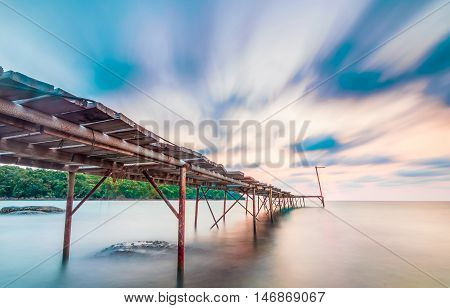 long explosure wood bridge at small island pier and smoothe clouds