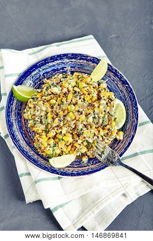 Homemade vegetarian mexican street food corn salad with cilantro, lime, mayonnaise, garlic, chili and cheese on blue vintage plate on stone background. Sweet, sour and hot tastes from mexican cuisine