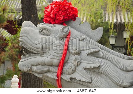 A stone chinese turtle head wrapped in a red ribbon at Jile temple (temple of bliss) in Harbin China in Heilongjiang province.