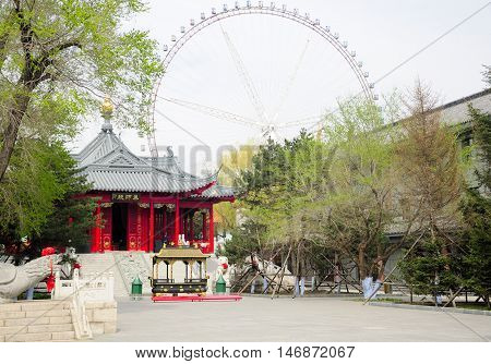 The Jile temple (temple of bliss) in Harbin China in Heilongjiang province with a ferris wheel in the background.