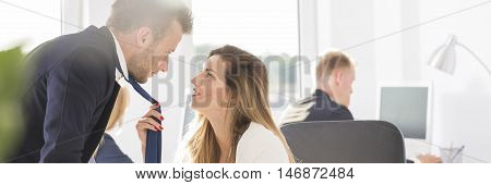 Sexy blonde businesswoman holding man's tie panorama
