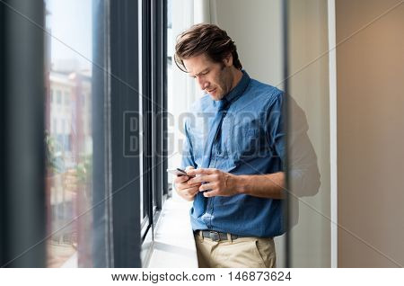 Young businessman using smartphone at office. Business man in formals texting with smart phone. Young man writing a phone meggage nera the window.