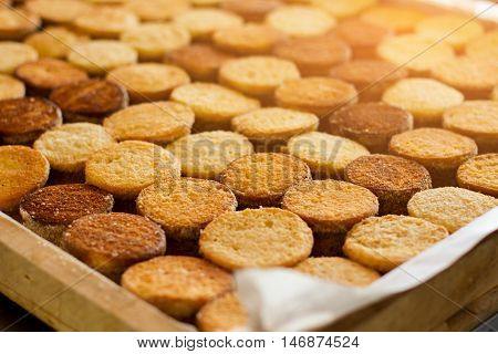 Rows of biscuits under sunlight. Yellow and brown cookies. Production of quality desserts. Shortcrust dough from the oven.