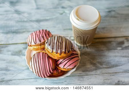 Glazed cookies near a cup. Colorful biscuits with glaze. Tea and bush cakes. Small meal in pastry cafe.