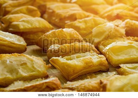 Puff pastry on wooden board. Lots of baked products. Income of cafe is growing. Dough without filling.