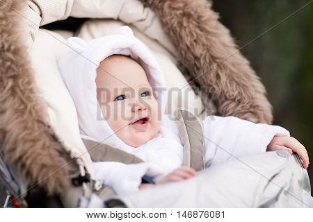 Happy laughing baby enjoying a walk in winter park sitting in a warm stroller with sheepskin hood