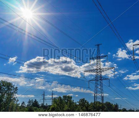 Power Line. pylon against a blue sky and sun