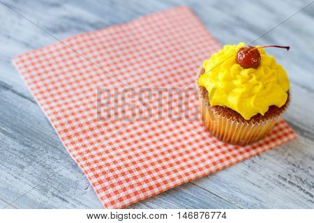 Yellow cupcake on a napkin. Red cherry on icing. Dessert served at the diner. How to lift mood.