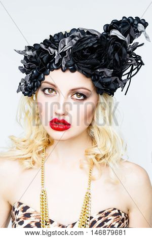 Portrait of beautiful young blonde woman in extravagant hat on white background