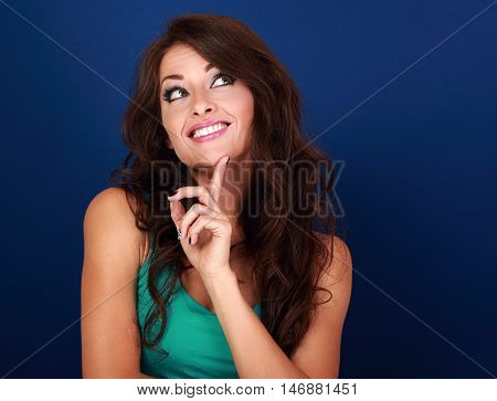 Concentrated Fun Grimacing Woman Thinking And Looking Up On Empty Space Background. Curly Brown Long