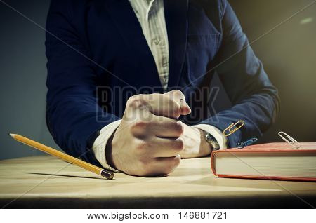Image of angry businessman. His fist beats on the table. From his blows stationery items: pencil a paper clip a bounced.