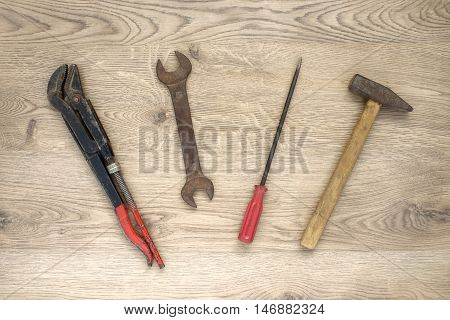 Rusty old hand tools on wooden background