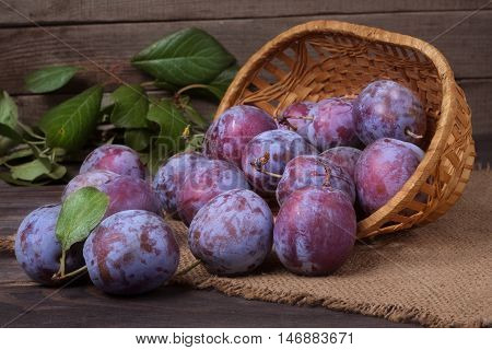 plum in a wicker basket on the wooden background with sackcloth .