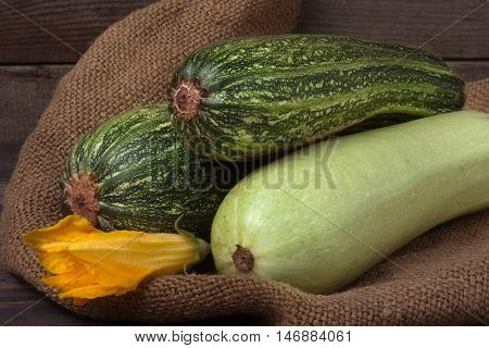 zucchini and courgette on sackcloth and wooden background with flower.