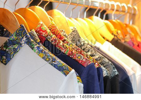 A row of batik colorful t-shirts, cloth, clothes, pants hanging on hangers. Traditional Indonesia