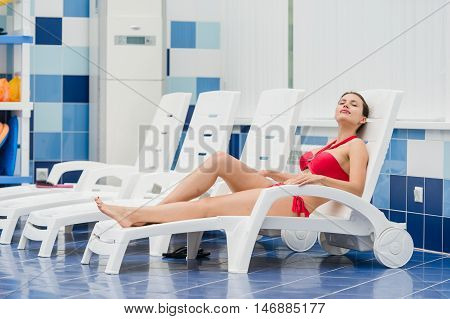 Body care. Woman with perfect body in red bikini lying on the deckchair by swimming pool in resort spa hotel