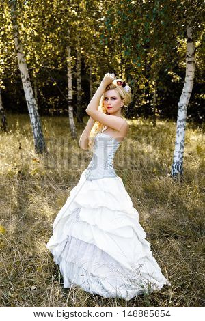 Blonde woman with long curly hair with flower accessory in antique corset and underwear