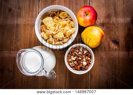 Light healthy breakfast: cornflakes, milk, apples and nuts for them. On wooden rustic table, top view, copy space