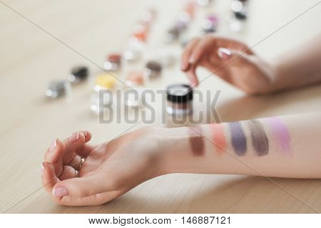 Female hand with eyeshadow colors. Closeup of woman makeup artist testing different eyeshadows, showing swatches