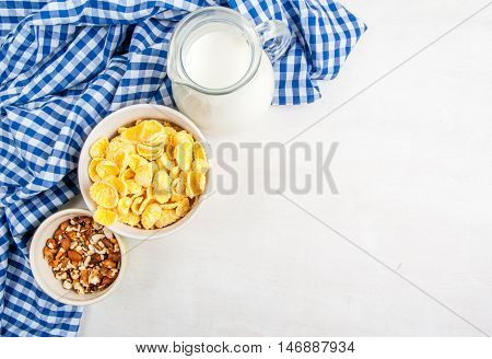 Light healthy breakfast: cornflakes, milk and nuts for them. On wooden white table, top view, copy space
