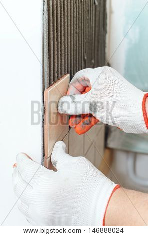 Worker putting tiles on the wall in the kitchen. Hi placing the tile on the adhesive.