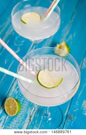 Classic Mexican Cocktail - Frozen Margarita in glass with cocktail tubes. Ingredients of cocktail - lime juice, ice, tequila, salt and orange liqueur. Aqua wood bacgkround.