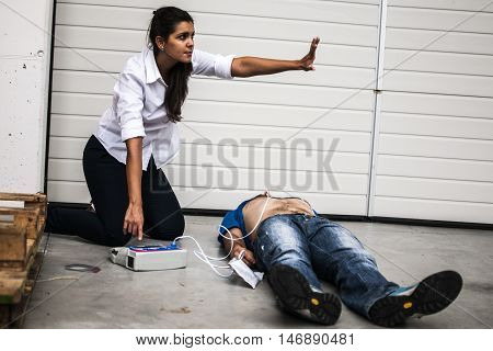 girl using a defibrillator for an unconscious man