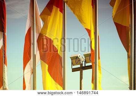 The Spanish and Polish flags against a blue sky with two floodlights.