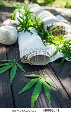 Leaves of cannabis and hemp cloth rollon the dark wooden surface. Hemp products. Agricultural technical culture