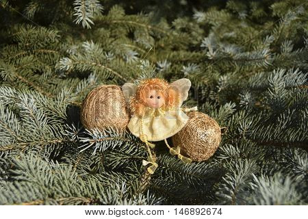 Christmas toy in the form of an angel and spheres. Toys are located on a fir-tree. An angel in white clothes. Spheres of gold color